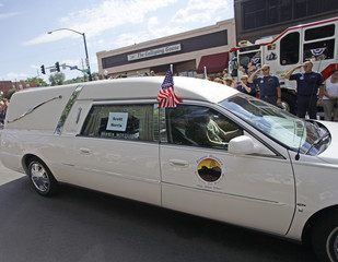 Firefighters salute a hearse carrying the remains of Norris as it moves in a motorcade from the Maricopa County Medical Examiner's office in Prescott, Arizona