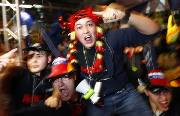 Supporters of Germany's Red Bull Formula One driver Sebastian Vettel celebrate after Vettel won his third drivers' world championship with the sixth place in the Brazilian F1 Grand Prix in Sao Paulo as they attend a public viewing session in Heppenheim