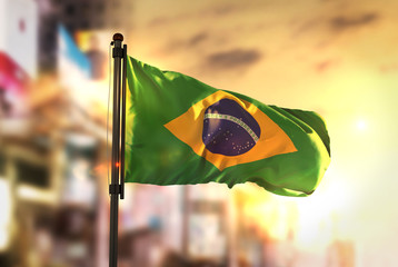 Foto op Plexiglas Brazilië Brazil Flag Against City Blurred Background At Sunrise Backlight