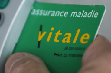 A photo illustration shows a French general practitioner using the health insurance card of a patient at a doctor's office in Bordeaux