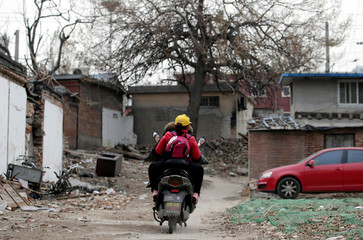 A woman rides an electric bike, carrying her daughter home in an old residential area in central Beijing