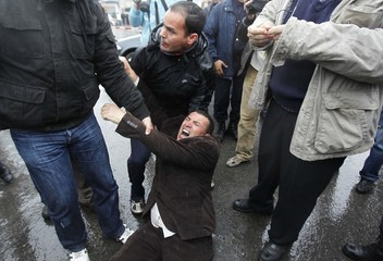 Plainclothes policemen detain a protester during a demonstration in Algiers