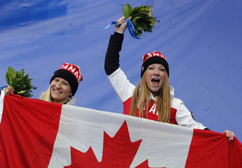 Canada's Humphries and Moyse celebrate during flower ceremony for women's bobsleigh event at 2014 Sochi Olympic Games