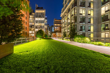 Highline promenade and lawn at twilight with city lights in the heart of Chelsea. Manhattan, New York City
