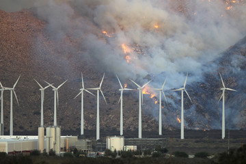 Fire spreads up the north side of the San Jacinto Mountains near wind turbines at the Silver Fire east of Banning, California
