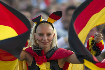 Germany supporter waves flags during public screening of Germany vs Portugal Euro 2012 soccer match in Berlin