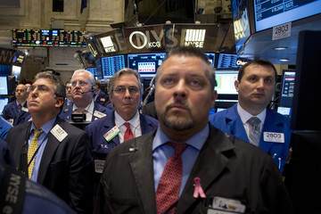 Traders pause during a moment of silence  on the floor of the New York Stock Exchange