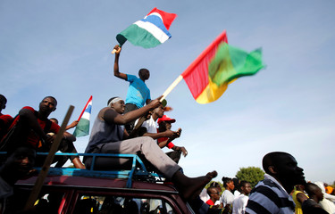 People celebrate the return of Gambia's new President Adama Barrow to the country, at the airport in Banjul