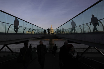 St Paul's Cathedral is seen during sunrise as pedestrians walk across the Millennium Bridge in the City of London