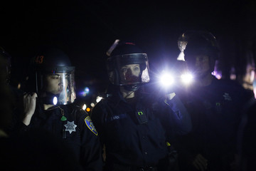 Police officers point flashlights toward a group of demonstrators on Highway 580 during a demonstration following the grand jury decision in the Ferguson, Missouri shooting of Michael Brown, in Oakland