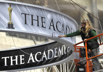 D'Angelo touches up with paint a sign in preparation for the 83rd Academy Awards in Hollywood