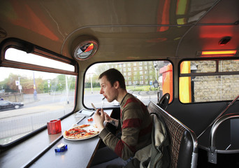 A diner eats pizza on the top deck of the Big Red Pizza Bus in Deptford, south east London
