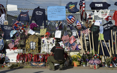 A firefighter reads memorial messages left for the fallen fighters at the memorial wall in Prescott Arizona