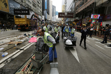 "Workers remove demolished obstacles during a clearance by the police at the last ""Occupy"" protest site blocking a main road at Causeway Bay shopping district in Hong Kong"