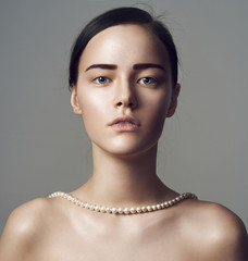 Portrait of beautiful sensual woman with holding in pearl jewelry.