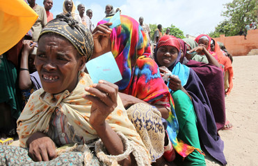 Internally displaced women queue to receive relief food from a distribution point in Somalia's capital Mogadishu
