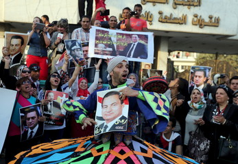 A dancer and supporter of ousted Egyptian president Hosni Mubarak performs a traditional Sufi (Al-Tannoura) Egyptian folk dance with his picture outside the area where he is hospitalized during his birthday in front of Maadi military hospital