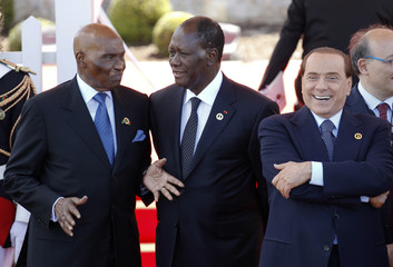 Ivory Coast's PR Ouattara talks with Senegal's PR Wade as Italy's PM Berlusconi smiles after a session of the G8 summit in Deauville