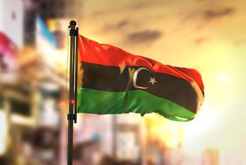 Libya Flag Against City Blurred Background At Sunrise Backlight