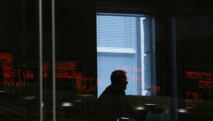 Man is seen through a glass window reflecting share prices displayed at Tokyo Stock Exchange in Tokyo