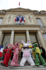 Life-size cartoon characters pose on the stairs of the Elysee Palace at the end of the Christmas party at the Elysee Palace, in Paris