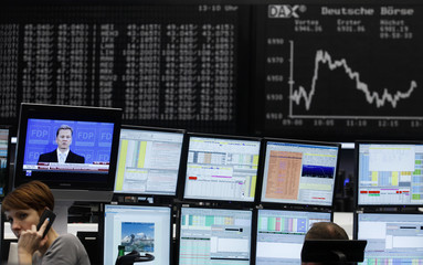 Trader are pictured at their desk next to a TV screen showing Westerwelle in front of the DAX board at the Frankfurt stock exchange