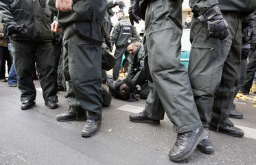 Police detain a protester during a demonstration next to a police station, where 3 refugees had been detained earlier on Friday, in Berlin