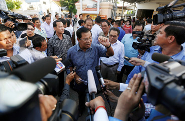 Cambodia's Prime Minister Hun Sen speaks to the media after registering for next year's local elections, in Kandal province