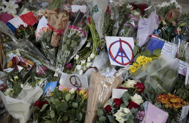 Flowers, drawings and messages are left in remembrance of the victims of the Paris attacks at the French Embassy in London