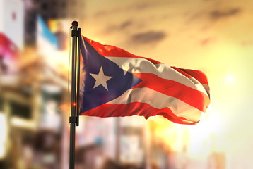 Puerto Rico Flag Against City Blurred Background At Sunrise Backlight