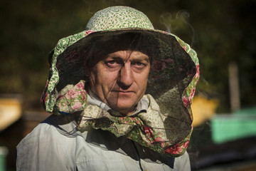 Circassian villager Muzarbek Teshu poses for a photograph as he attends to his bee hives in the village of Tkhagapsh in the Lazerevskoye district of Sochi