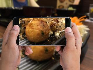 man holding smartphone taken Takoyaki; Japanese food photo on the table to share social network