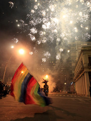 A reveller waves a flag as fireworks explode during a gay pride parade in downtown Montevideo