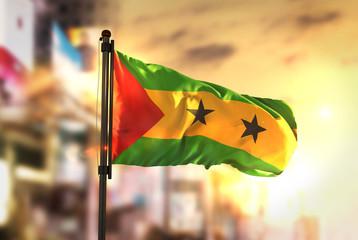 São Tomé and Príncipe Flag Against City Blurred Background At Sunrise Backlight