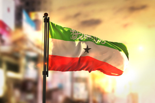 Somaliland Flag Against City Blurred Background At Sunrise Backlight