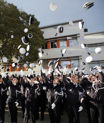 Police students throw their hats during the graduation ceremony at the National Police Academy in Nimes