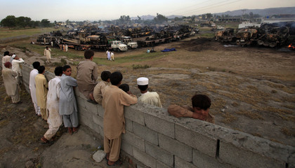 Residents look at damaged trucks after they were attacked and burnt in a field in Sangjani, located in the outskirts of Islamabad