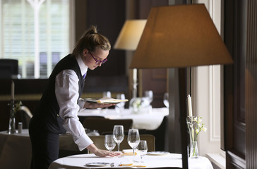 Commis de Rang Connolly poses for a photograph as she sets the table in the Strathearn Restaurant at the Gleneagles Hotel in Scotland