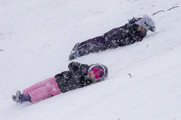 Girls roll down a hill at a golf course during a snow storm in Pelham Manor, New York