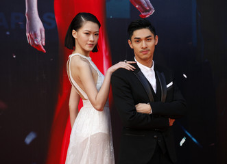 Hong Kong actor Kwan poses with Malaysian actress Liew on the red carpet during 33rd Hong Kong Film Awards in Hong Kong