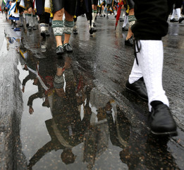 People dressed in traditional Bavarian clothes are reflected in puddle while taking part in Oktoberfest parade in Munich
