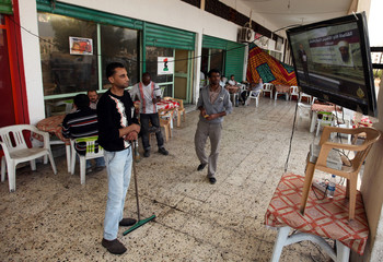 Libyans follow the news on TV about the death of Osama bin Laden in Benghazi