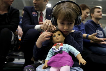 Anne-Sophie Marquis strokes the hair of her doll Clare, wearing a button supporting U.S. Republican presidential candidate Trump at a Trump campaign rally in Plymouth