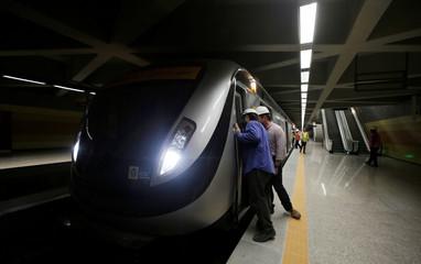Workers observe a train at the new subway station in Barra da Tijuca neighborhood, which is part of the Rio de Janeiro's metro line 4 under construction to connect Barra da Tijuca and Ipanema neighborhoods, ahead of the Rio 2016 Olympics in Rio de Janeiro