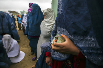 Afghan women wait in line to cast their ballots at a polling station in Mazar-i-Sharif