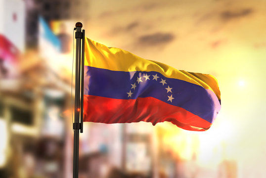 Venezuela Flag Against City Blurred Background At Sunrise Backlight
