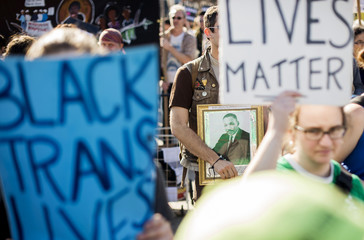 Man carries a picture of Martin Luther King during a protest march through Oakland, California