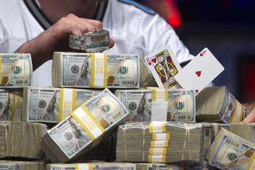 Riess' winning hand is shown amongst stacks of money after Riess won the World Series of Poker $10,000 buy-in no-limit Texas Hold 'Em tournament in Las Vegas, Nevada