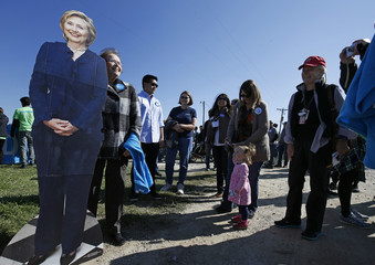 Supporters of former U.S. Secretary of State Hillary Clinton line up to have their picture taken with a cardboard cutout of Clinton at the 37th Harkin Steak Fry in Indianola, Iowa