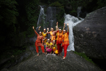 "Hindu devotees pose as their friend takes pictures of them in front of the waterfall during the ""Bol Bom"" pilgrimage in Kathmandu"